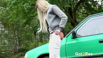 Bright blondhead in white trousers lies near the orange motor vehicle and pisses