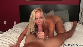 Naked MILF stands nude and throats a generous cock while being taped