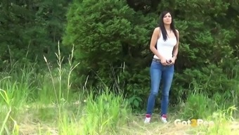 Playful brunette gal in blue jeans Rebecca pees in the woodland