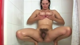 Brunette stunner acts with her big tits then hands wrists and fingers her hirsuite twat while you are having a shower